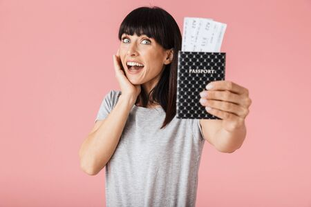 Image of a beautiful amazing excited happy woman posing isolated over light pink background wall holding passport with tickets. Stock Photo