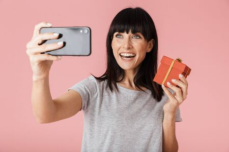 Image of a beautiful shocked amazing excited happy woman posing isolated over light pink background wall using mobile phone take a selfie holding present box.