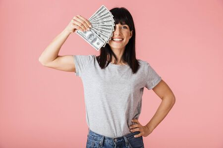 Image of a beautiful amazing excited happy woman posing isolated over light pink background wall holding money. Stock Photo
