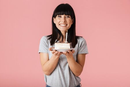 Image of a beautiful young woman posing isolated over pink wall background holding holiday birthday cake.