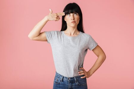 Image of a beautiful amazing displeased woman posing isolated over light pink background wall showing gun gesture.