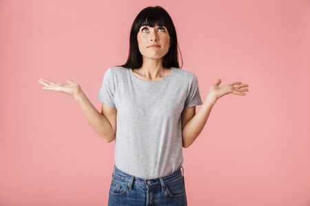 Image of a beautiful confused woman posing isolated over light pink background wall.