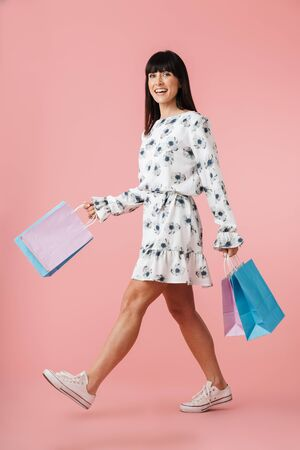 Image of a beautiful excited young woman isolated over pink wall background with shopping bags.