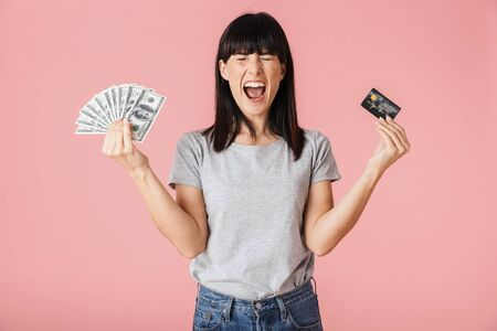 Image of a beautiful amazing excited happy woman posing isolated over light pink background wall holding money and credit card.