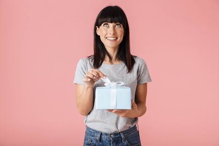 Image of a beautiful amazing excited happy woman posing isolated over light pink background wall holding present gift box.