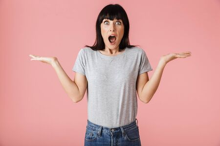 Image of a beautiful excited woman posing isolated over light pink background wall showing copyspace. Stock Photo