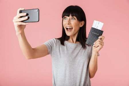 Image of a beautiful shocked amazing excited happy woman posing isolated over light pink background wall using mobile phone take a selfie holding passport with tickets.