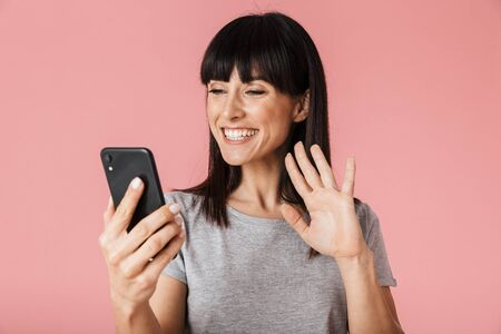 Image of a beautiful amazing excited happy woman posing isolated over light pink background wall using mobile phone talking waving. Stock Photo