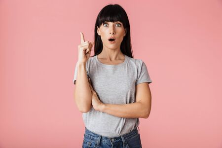 Image of a beautiful amazing shocked woman posing isolated over light pink background wall pointing have an idea.