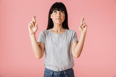 Image of a beautiful amazing emotional nervous woman posing isolated over light pink background wall showing hopeful please gesture.