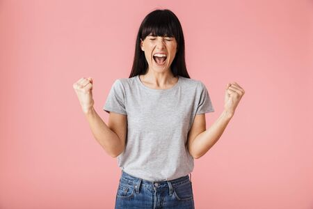 Image of a beautiful amazing happy excited woman posing isolated over light pink background wall make winner gesture.