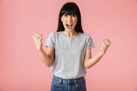 Image of a beautiful amazing screaming excited woman posing isolated over light pink background wall make winner gesture.