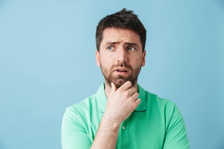 Image of a thinking serious young handsome bearded man posing isolated over blue wall background.