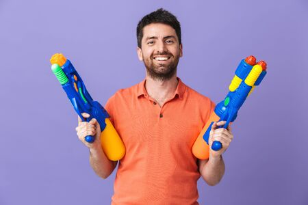 Image of a happy young handsome bearded man posing isolated over violet purple wall background holding water gun summer beach toy.