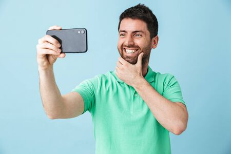 Portrait of a handsome bearded man wearing casual clothing standing isolated over blue background, taking a selfie