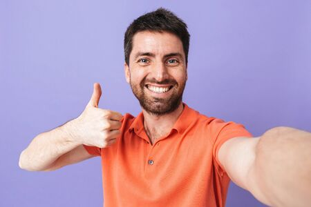 Image of a happy young handsome bearded man posing isolated over violet purple wall background take selfie by camera showing thumbs up.