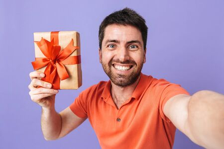 Image of a happy young handsome bearded man posing isolated over violet purple wall background take selfie by camera holding present gift box.