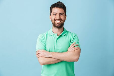 Image of a happy young handsome bearded man posing isolated over blue wall background.