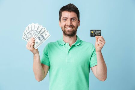 Image of excited young handsome bearded man posing isolated over blue wall background holding money and credit card. 스톡 콘텐츠