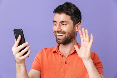 Image of a happy young handsome bearded man posing isolated over violet purple wall background talking by mobile phone waving. 스톡 콘텐츠