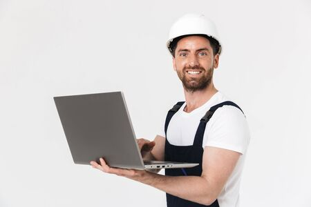 Confident happy bearded builder man wearing overalls and hardhat standing isolated over white background, using laptop computer