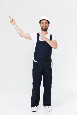 Full length of a confident bearded builder man wearing overalls and hardhat standing isolated over white background, pointing finger at copy space Imagens