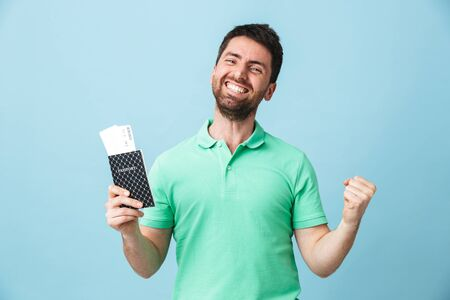 Portrait of a handsome bearded man wearing casual clothing standing isolated over blue background, showing passport with flight tickets, celebrating