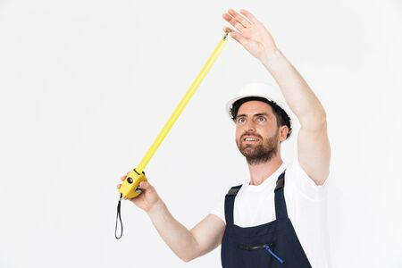 Portrait of a handsome bearded builder man wearing overalls standing isolated over white background, using measuring tape