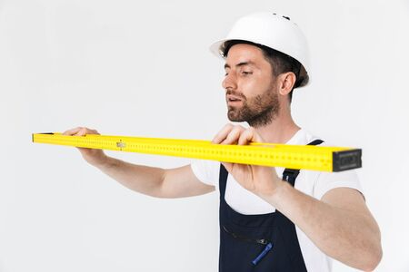 Confident bearded builder man wearing overalls and hardhat standing isolated over white background, carrying measurement level