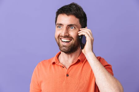 Image of a happy young handsome bearded man posing isolated over violet purple wall background talking by mobile phone. 스톡 콘텐츠