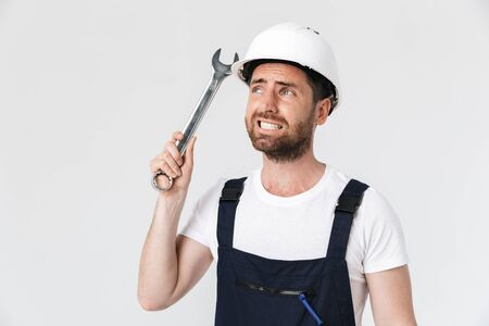 Confused bearded builder man wearing overalls and hardhat standing isolated over white background, showing adjustable wrench