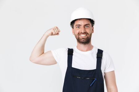 Confident bearded builder man wearing overalls and hardhat standing isolated over white background, flexing muscles Imagens