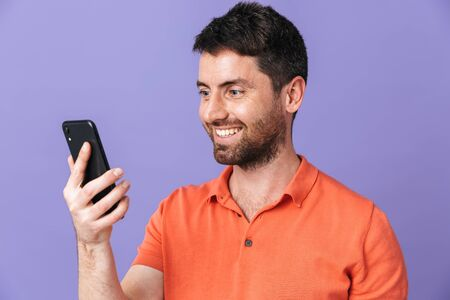 Image of a happy young handsome bearded man posing isolated over violet purple wall background using mobile phone.