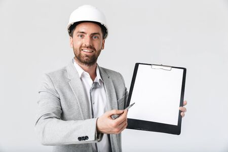 Confident bearded man builder wearing suit and hardhat standing isolated over white background, showing blank notepad