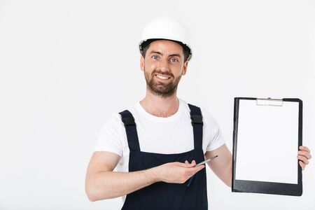 Confident bearded builder man wearing overalls and hardhat standing isolated over white background, showing blank tablet