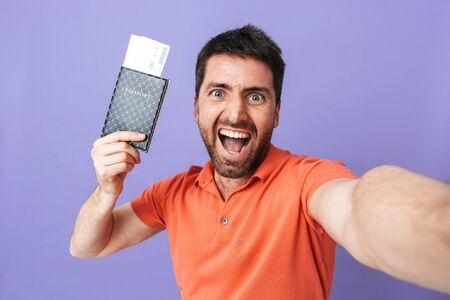 Image of a happy young handsome bearded man posing isolated over violet purple wall background take selfie by camera holding passport with tickets.
