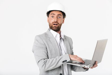 Confused bearded man builder wearing suit and hardhat standing isolated over white background, showing laptop computer Reklamní fotografie