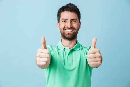 Portrait of a happy handsome bearded man wearing casual clothing standing isolated over blue background, thumbs up