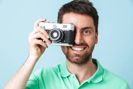 Portrait of a handsome bearded man wearing casual clothing standing isolated over blue background, taking a picture with photo camera Banque d'images