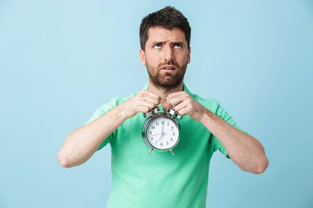Image of displeased young handsome bearded man posing isolated over blue wall background holding alarm clock. Stock fotó