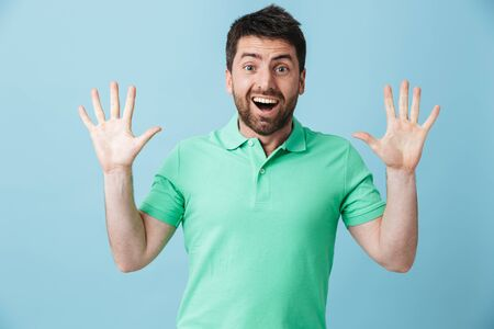 Image of a happy surprised young handsome bearded man posing isolated over blue wall background. 스톡 콘텐츠
