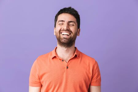 Image of a happy young handsome bearded man posing isolated over violet purple wall background. 스톡 콘텐츠