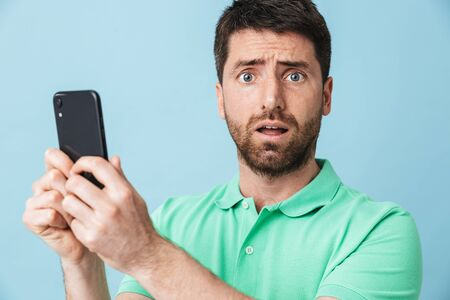 Image of a shocked scared young handsome bearded man posing isolated over blue wall background using mobile phone.