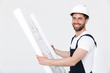 Portrait of a handsome bearded builder man wearing overalls standing isolated over white background, looking at the draft Imagens