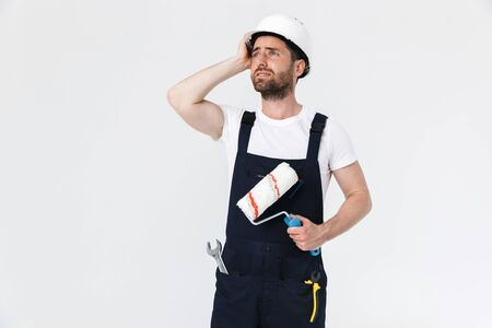 Portrait of a confused handsome bearded builder man wearing overalls standing isolated over white background, holding paint brush Imagens