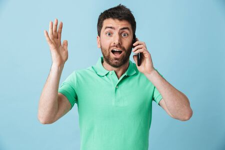 Image of a shocked emotional young handsome bearded man posing isolated over blue wall background talking by mobile phone.