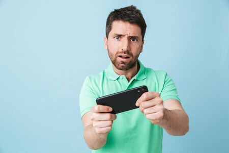 Image of a excited emotional young handsome bearded man posing isolated over blue wall background play games by mobile phone.