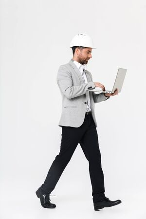 Full length of a confident bearded man builder wearing suit and hardhat standing isolated over white background, using laptop computer