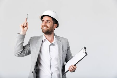 Confident bearded man builder wearing suit and hardhat standing isolated over white background, holding blank notepad, pointing finger up