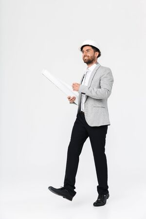Full length of a confident bearded man builder wearing suit and hardhat standing isolated over white background, carrying blueprints Imagens